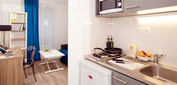 A kitchen area with a hot plate, refrigerator, microwave oven, dishes, etc